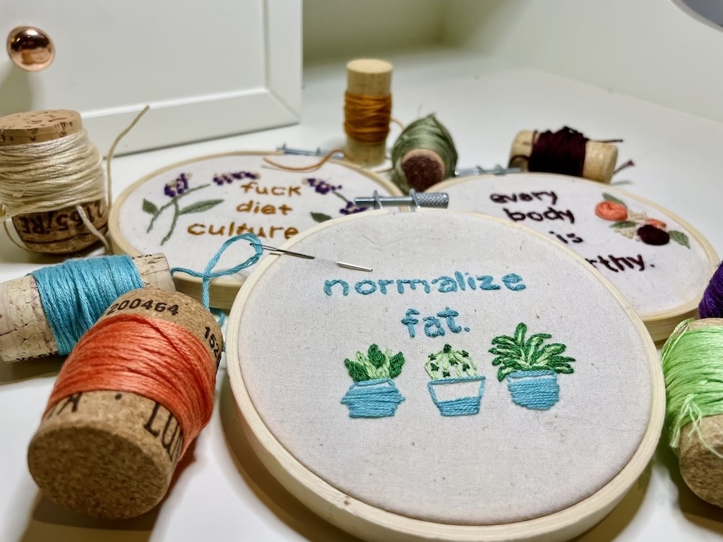 "three 4"" embroidery hoops with unbleached muslin fabric, embroidered in multiple colors with the messages ""fuck diet culture,"" ""every body is worthy"" and ""normalize fat"", surrounded by spools of thread on a white surface."